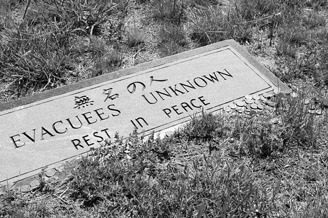 A black and white photograph of a headstone reading EVACUEES UNKNOWN, REST IN PEACE beneath Japanese characters; there is a pile of coins in one corner