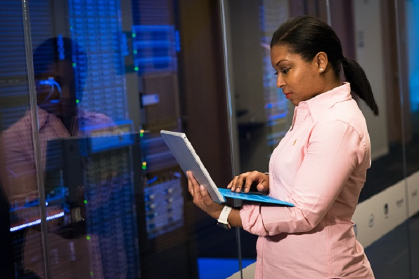 a photograph of an African-American woman holding a laptop while standing in front of a bank of computer equipment