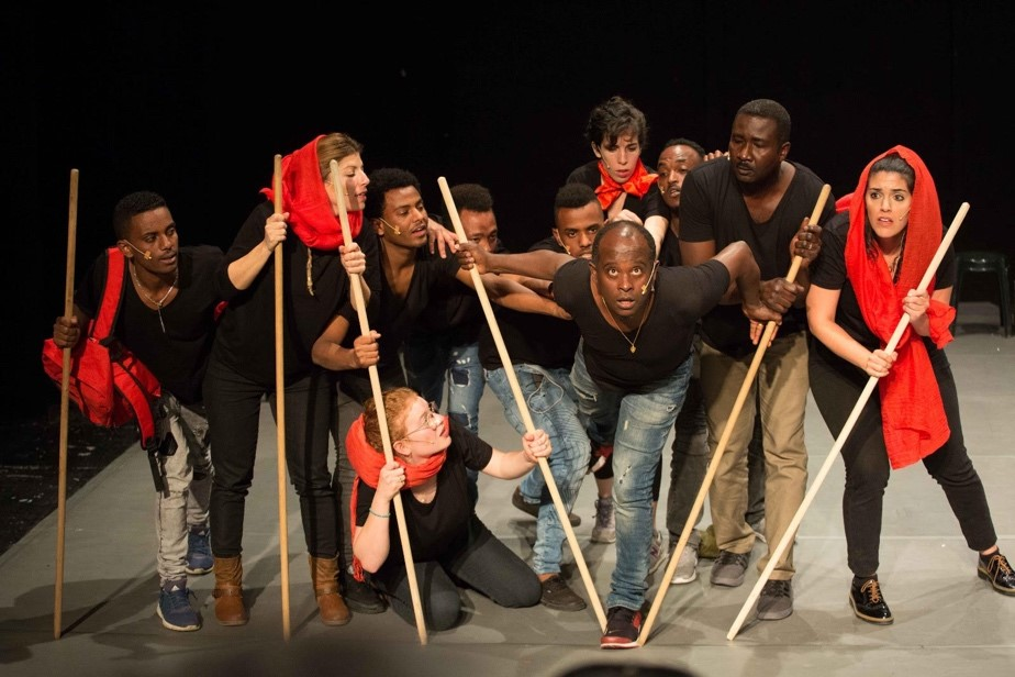 A mixed-race group of individuals, some with red scarves on their heads, all holding long poles