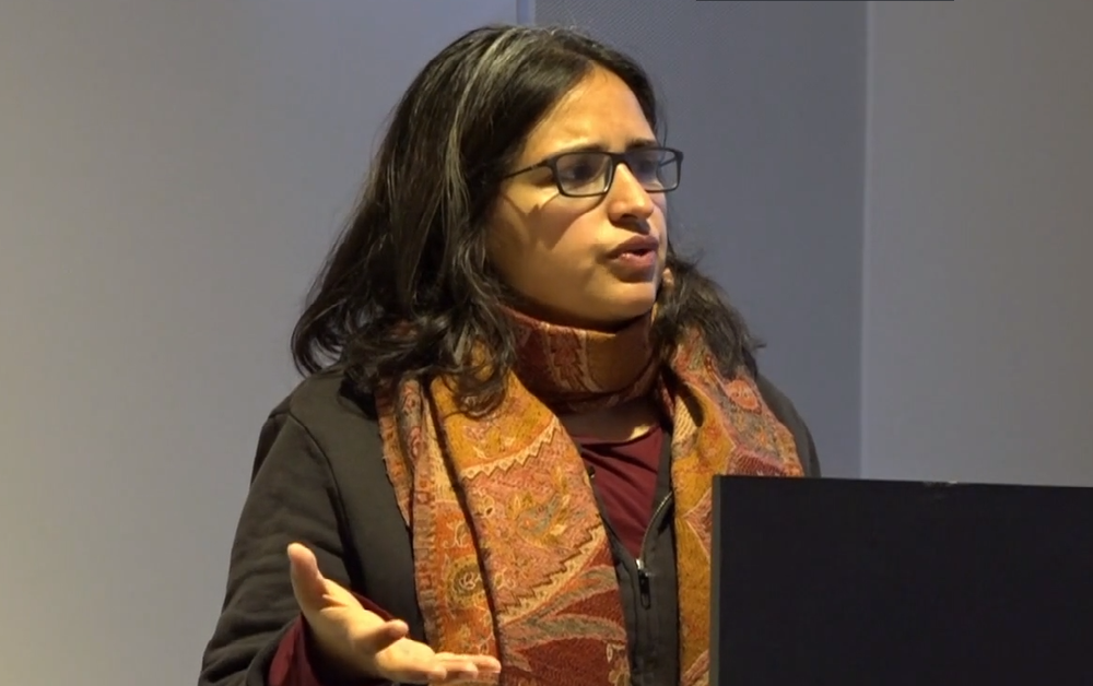 a photograph of a woman with brown hair (Harsha Walia) speaking at a podium