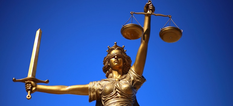 a low-angle perspective of a golden statue of Lady Justice against a blue sky