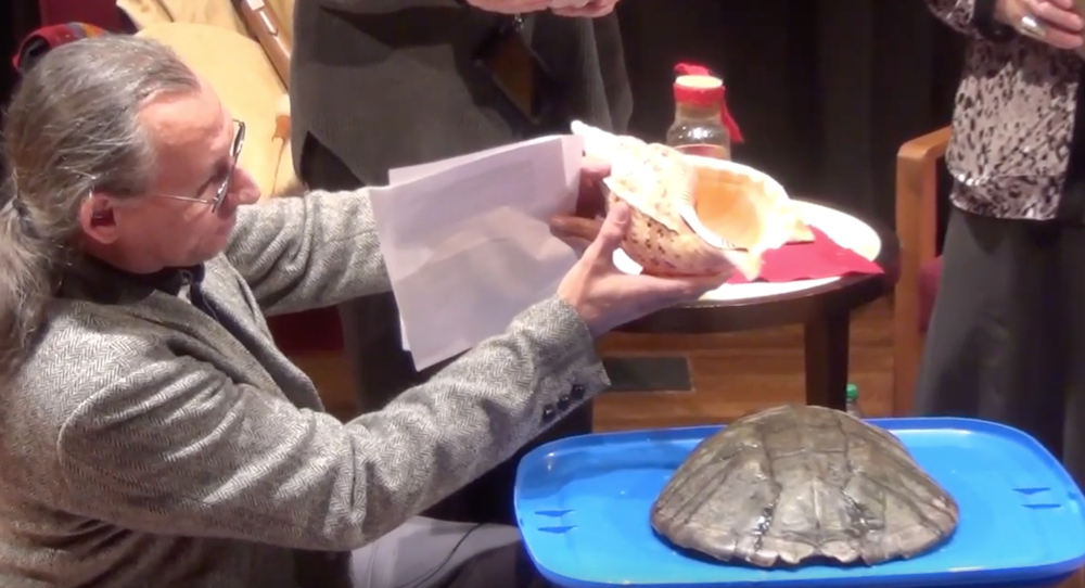 a frame from a color video showing a man with long gray hair kneeling next to a small pedestal that holds a turtle shell on a blue tray; he is pouring water onto the shell from a large seashell