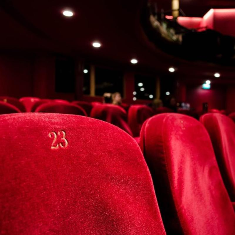a photograph of empty red velvet theatre seats