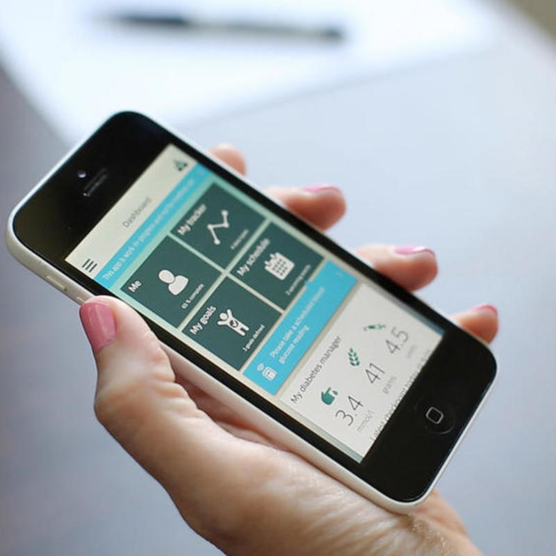 a photograph of a hand holding a smart phone displaying a health management app