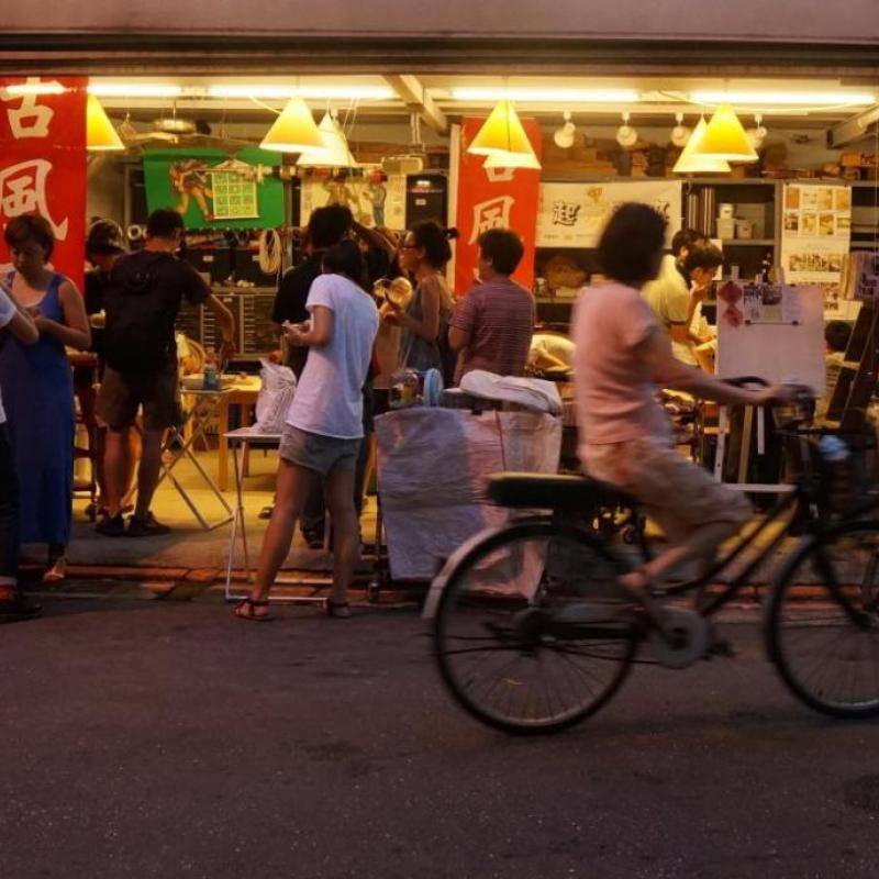 people congregating on a Taiwanese street in front of an outdoor market; a woman rides by on a bicycle