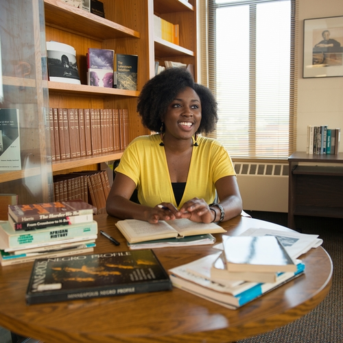 A young black woman at a table with books